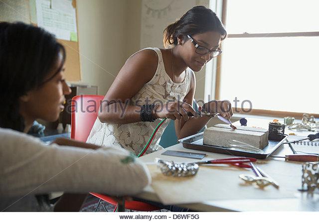 Weiblichen Schmuck Künstler mit Taschenlampe mit Kollegen im Vordergrund Stockbild