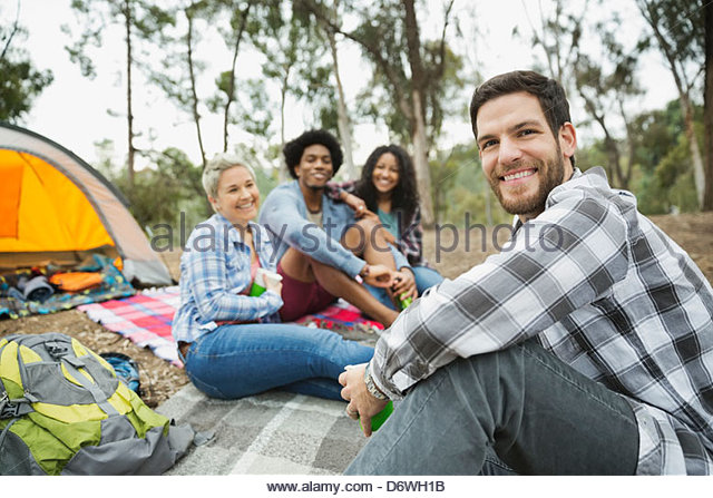 Porträt von Mitte erwachsener Mann sitzen mit Freunden beim camping Stockbild