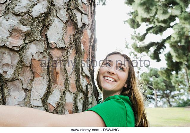 Glückliche junge Frau wegschauen während umarmt Baum im park Stockbild