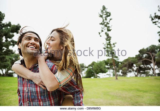 Glücklicher Mann geben Freundin eine Huckepack Fahrt im park Stockbild