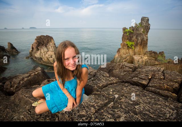 Teengirl in einem blauen Kleid in den Felsen der Küste in Thailand. Stockbild