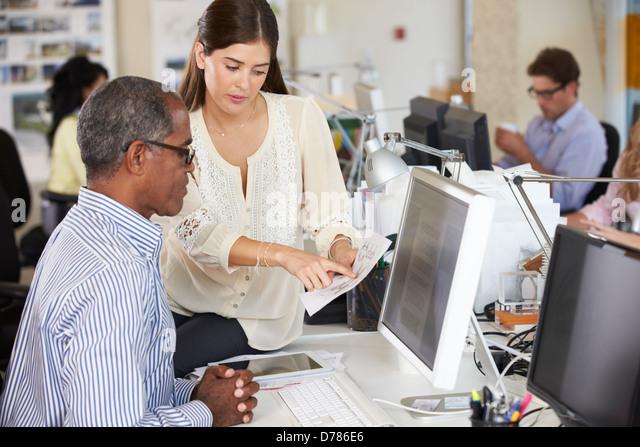 Arbeiter an Schreibtischen In belebten Kreativbüro Stockbild