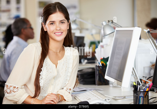 Frau am Schalter In belebten Kreativbüro Stockbild