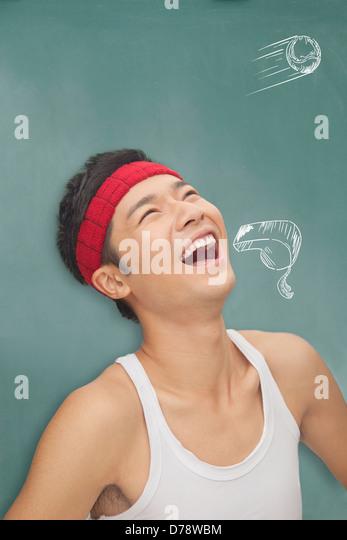 Junger sportlicher Mann vor Tafel mit Zeichnungen Stockbild