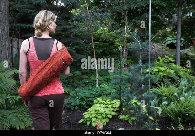 Frau praktizieren Yoga im Garten Stockbild