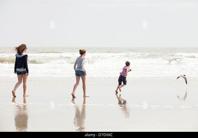 Familie mit 3 spielen am Strand Stockbild