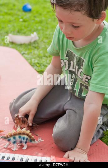 Bildnis eines Knaben mit Tastatur spielen im Freien im Garten. Stockbild