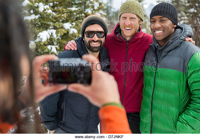 Menschen nehmen Foto von Freunden draußen im winter Stockbild