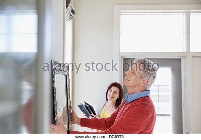 Älteres paar hängende Kunstwerk im neuen Zuhause Stockbild
