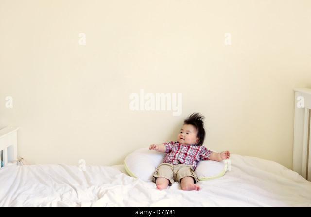 Koreanische amerikanische Kind mit stacheligen Haaren auf Bett ausgestreckten Armen - Stock-Bilder