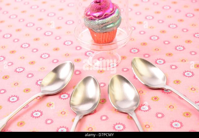 Fehlerhaft-Konzept mit einem bunten Cupcake und vier Löffel essen Stockbild
