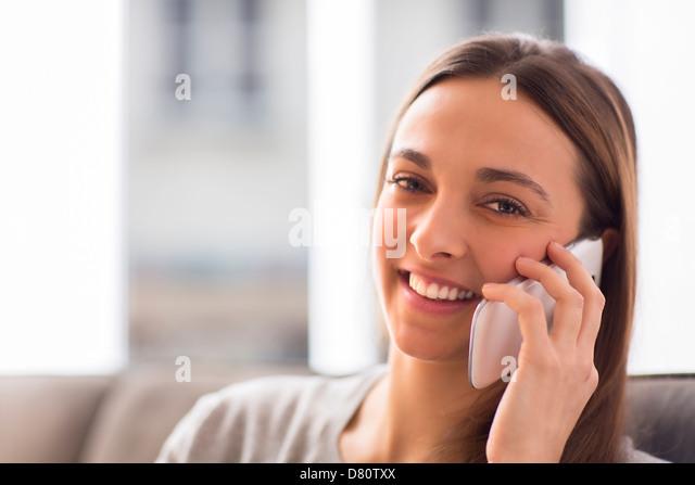 Hübsche junge Frau mit weißen Smartphone zu Hause schaut in die Kamera Stockbild
