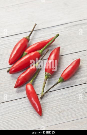 Sieben rote Thai-Chilischoten auf rustikale Oberfläche des Holzes. Stockbild
