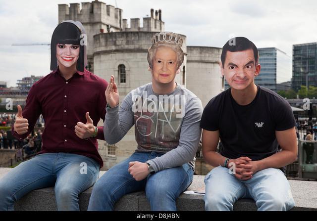Touristen tragen Celebrity und royal Gesichtsmasken. Jessie J, ihre Majestät Königin Elizabeth II und Stockbild