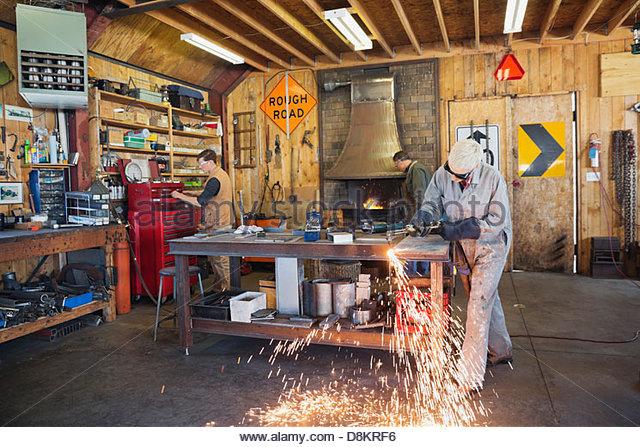 Weibliche Schweißer mit Schweißbrenner in Werkstatt Stockbild
