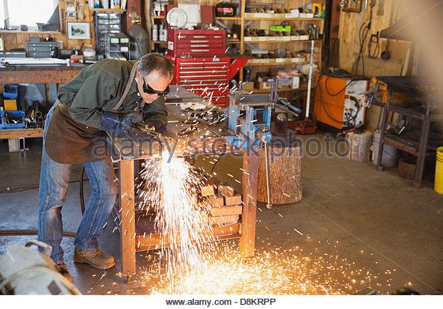 Schweißer mit Taschenlampe an Werkbank in Werkstatt Stockbild