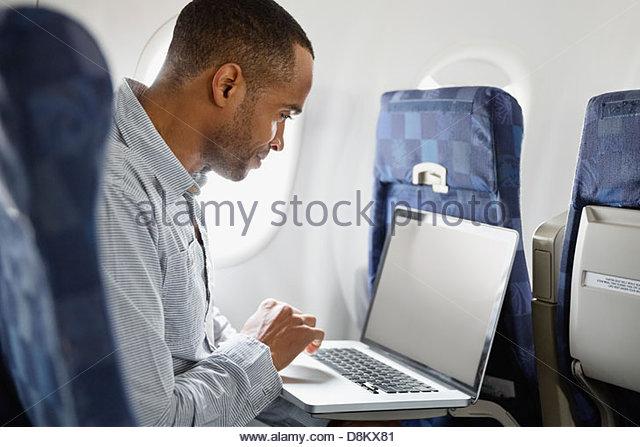 Mann mit Laptop im Flugzeug - Stock-Bilder