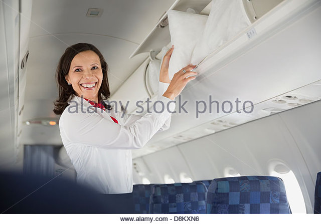 Flight Attendant Einnahme Kissen aus Gepäckfach im Flugzeug Stockbild