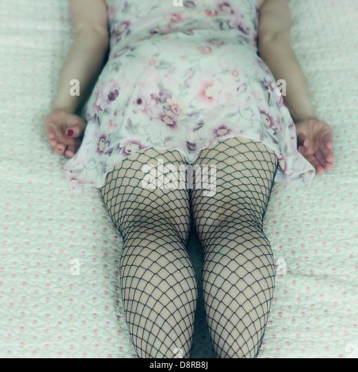 eine Frau in einem Negligé ist auf einem Bett liegend. Stockbild