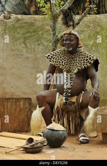 Zulu Häuptling in feierlichen Kleid sitzt neben Topf mit traditionellen Sorghum Bier Shakaland KwaZulu-Natal Stockbild