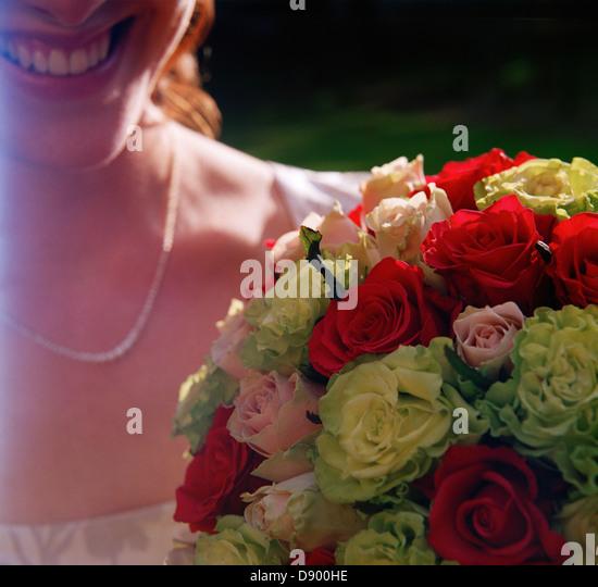 Eine lächelnde Braut hält einen Hochzeitsstrauß, Schweden. Stockbild