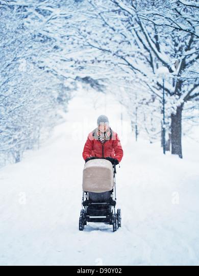 Lächelnde Mutter mit Kinderwagen an Winterlandschaft wandern Stockbild