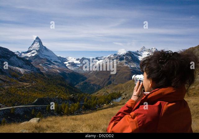Eine Frau im roten Jacke ein Bild des Matterhorns; Frau in Roter Jacke Richtet Ihre Video-Kamera Auf Das Matterhorn Stockbild