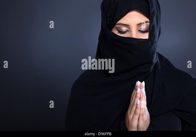 geheimnisvolle orientalische Frau beten auf schwarzem Hintergrund Stockbild