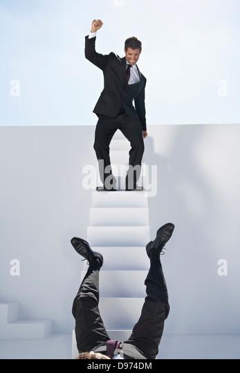 Geschäftsmann, stehend auf Treppen und andere fallen Stockbild