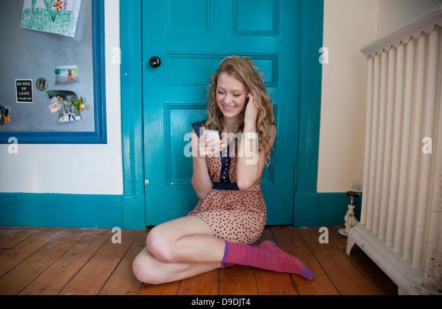Teenager sitzen vor blaue Tür mit Mobiltelefon Stockbild