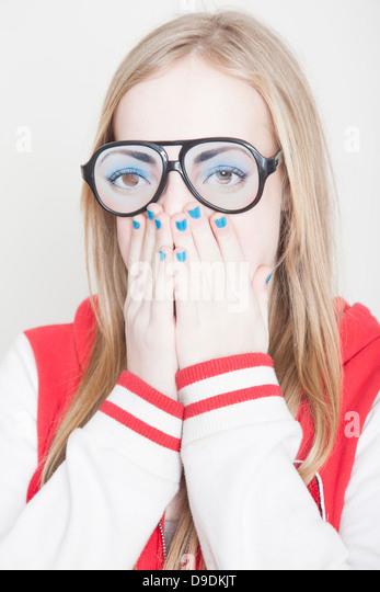 Mädchen tragen gefälschte Brillen mit Händen, die ihr den Mund zu Stockbild
