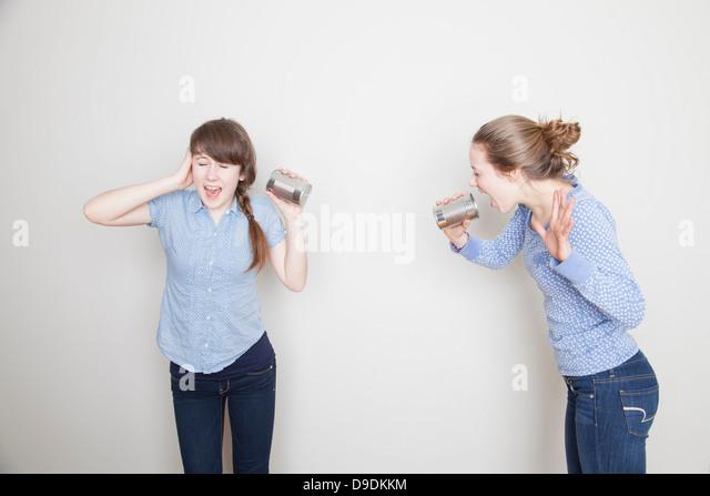 Zwei Mädchen mit Blechdosen, schreien und ihr Ohr abdecken Stockbild