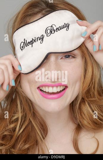Teenager-Mädchen mit Dornröschen Augenmaske auf Kopf, über Auge Stockbild