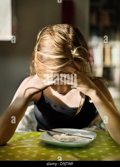 Teenager-Mädchen sitzen auf Platte mit Kopf in Händen Stockbild
