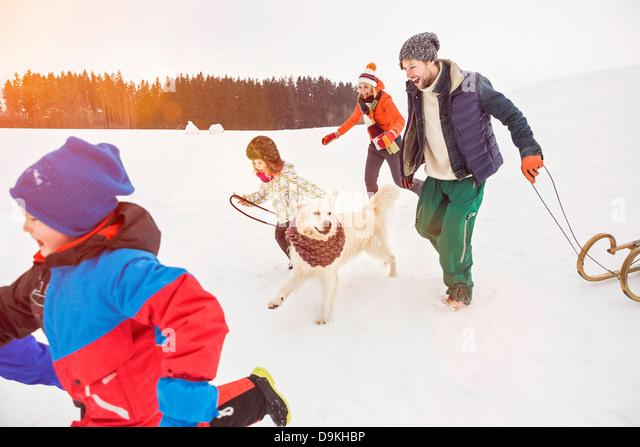 Familie im Schnee mit Hund laufen Stockbild