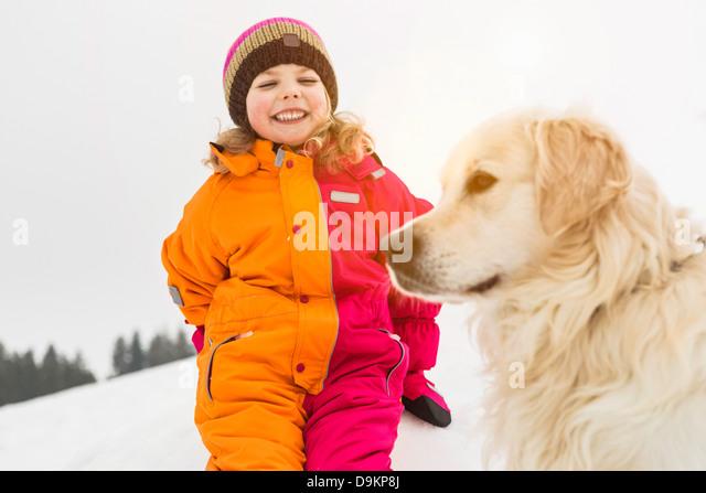 Mädchen tragen Winterkleidung mit Hund Stockbild