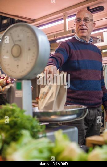 Ladenbesitzer mit einem Gewicht von frischem produzieren im Markt Stockbild