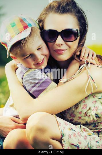 Schöne Mutter umarmt ihren niedlichen kleinen Sohn Stockbild