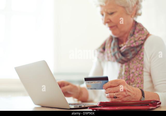 Großmutter mit einer Kreditkarte zu einer Online-Transaktion Stockbild