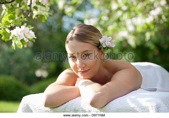Eine junge Frau, die Verlegung auf einem Massagetisch mit Apfelblüte im Haar, Lächeln Stockbild