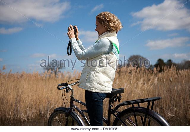Eine reife Frau mit dem Fotografieren während Sie Radfahren Stockbild