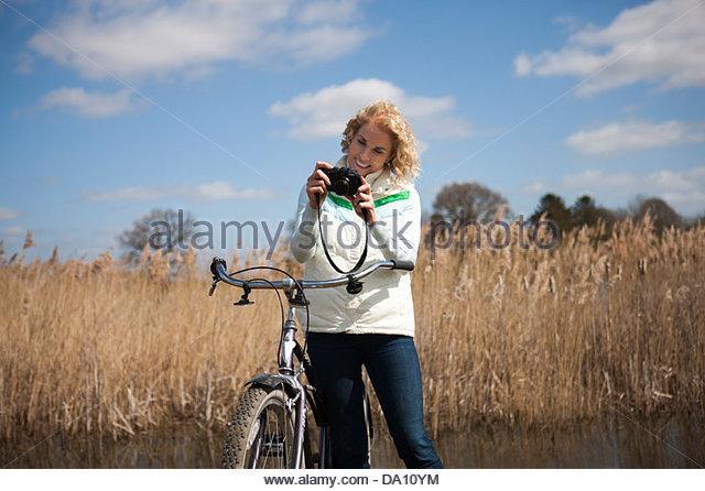 Eine reife Frau, die eine Kamera betrachten, während Sie Radfahren Stockbild