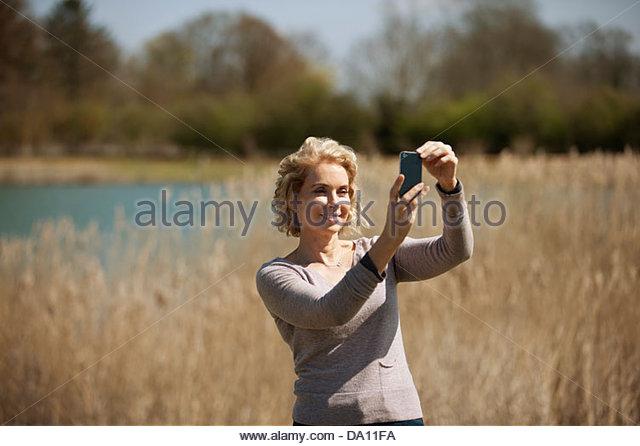 Eine reife Frau auf dem Lande, ein Foto mit einem smartphone Stockbild