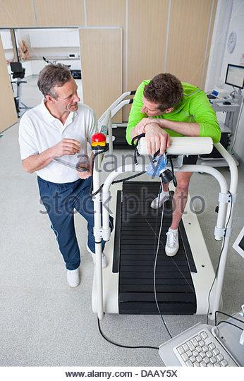 Sportwissenschaftler im Gespräch mit Läufer mit Maske auf Laufband im Labor Stockbild