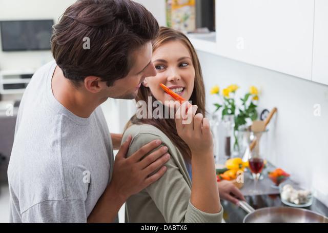 Attraktive Frau, die ihr Mann Paprika füttern Stockbild