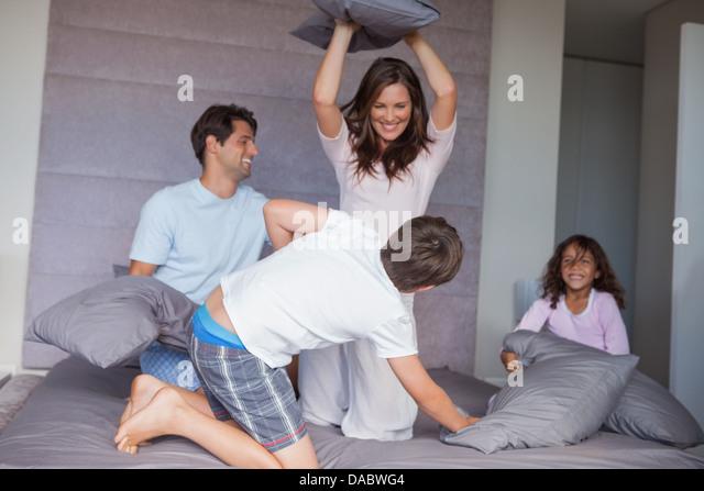 Familie mit einem Kissen auf dem Bett zu kämpfen Stockbild