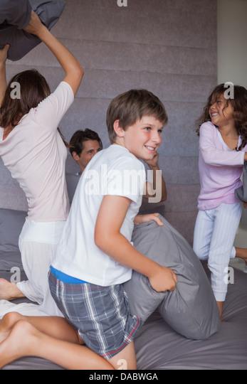 Glückliche Familie mit einem Kissen auf dem Bett zu kämpfen Stockbild