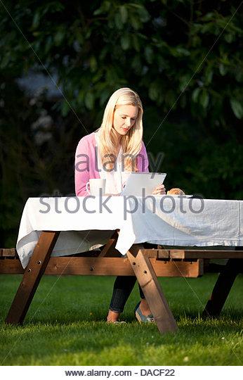 Eine junge, blonde Frau sitzt auf einer Gartenbank mit einem digitalen tablet Stockbild