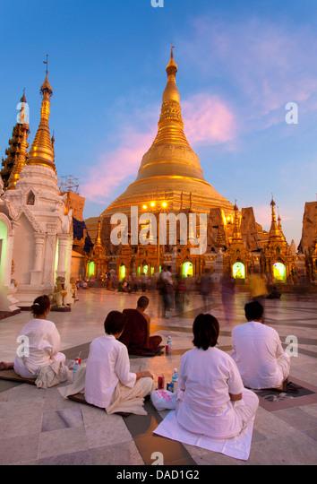 Shwedagon Paya (Pagode) in der Abenddämmerung mit buddhistischen Gläubigen beten, Yangon (Rangoon), Myanmar Stockbild