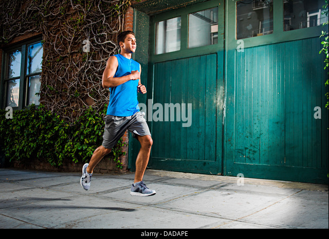 Junger Mann läuft auf städtischen Straße Stockbild